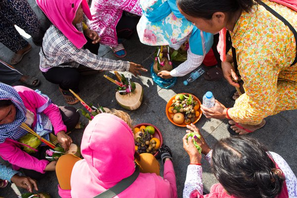 Cambodian women make fruit offerings to spirits at a temple in Phnom Penh thumbnail