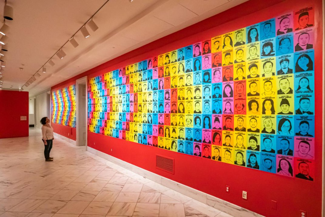 A person looks at a hallway covered in a collage of portraits