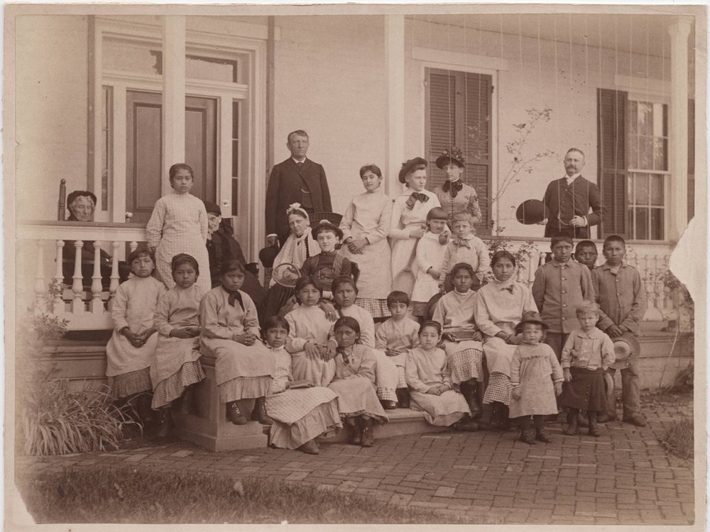 A sepia toned image of a group of young women, with a few young boys and girls, sitting in front of a white house on a porch. Pratt stands in dark garb behind the group