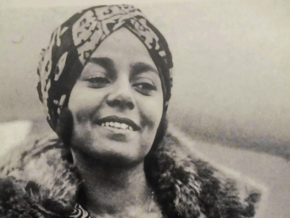 Black-and-white photograph of Stephanie St. Clair, smiling while looking away from the camera