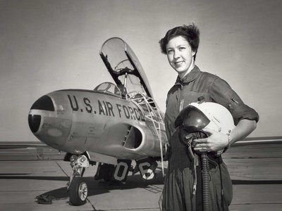 An undated photograph shows Wally Funk standing with a U.S. Air Force jet.