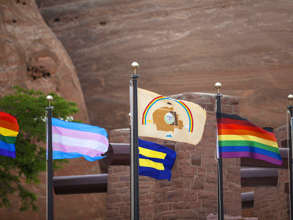 Various Pride flags (rainbow, transgender, equality, LGBTQ+ people of color, and love rainbow) displayed alongside the Navajo Nation flag in Window Rock, Arizona. (Photo by Pamela J. Peters (Diné)/Táchii'nii Photography, used with permission)