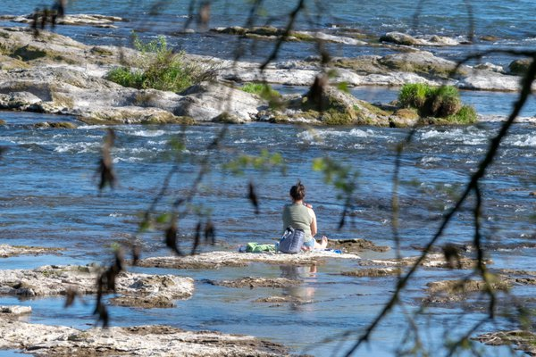Woman sunbathes in an isolated spot in the river thumbnail