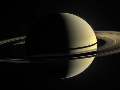 In the image captured by Cassini, the rings are illuminated both by direct sunlight and by light reflected off Saturn's cloud tops.