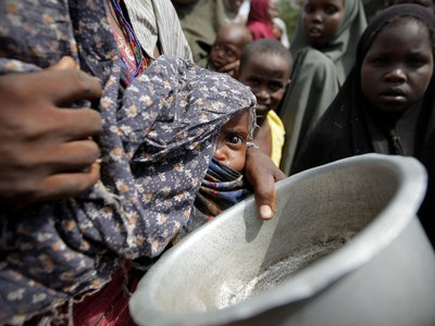 A malnourished Somalian baby is held by its mother while waiting for food during a 2011 drought.