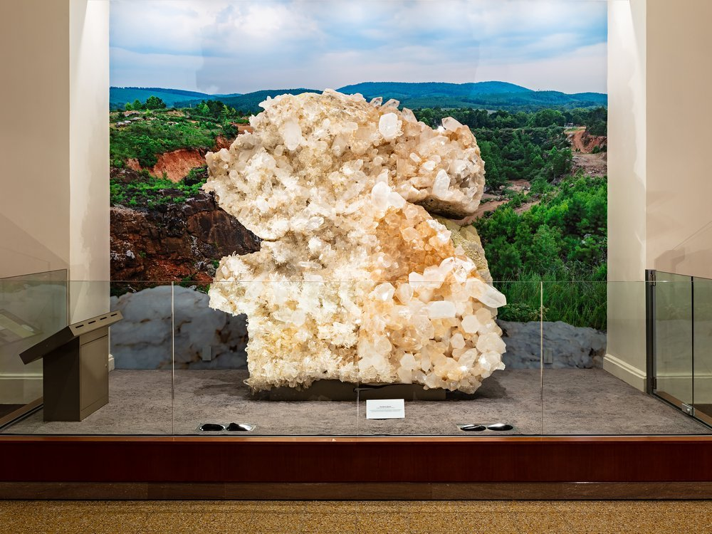 Museum display of the Berns Quartz from the front. The specimen is behind counter-height glass with a backdrop of Arkansas' Ouachita Mountains.
