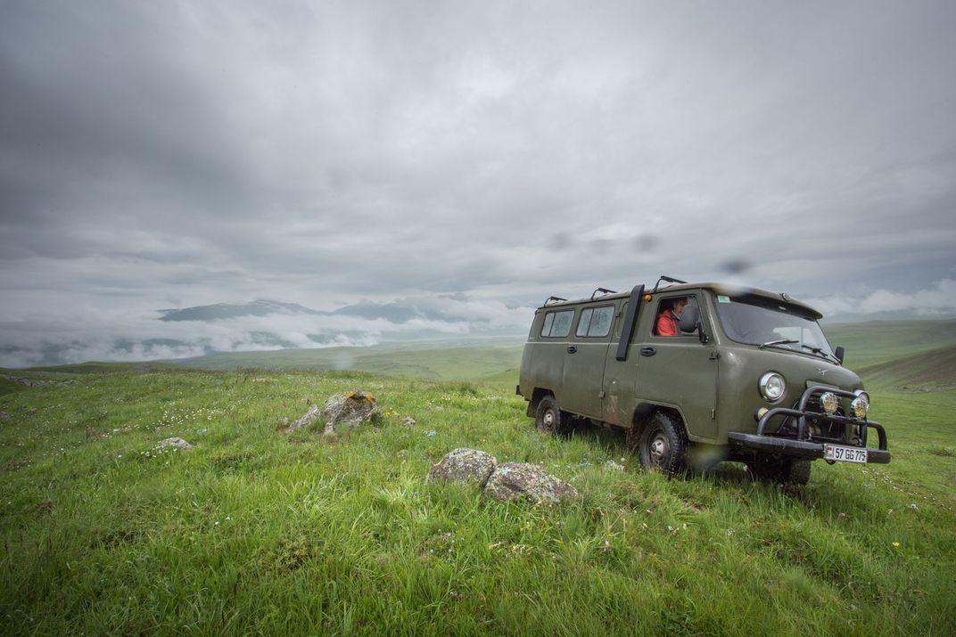 A vintage, dark green van drives through a misty field atop a mountain.