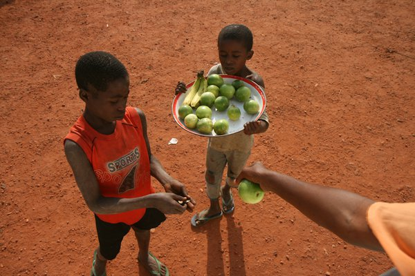 Fruit sellers. These boys wait for passing vehicles and try to sell fruits to passengers and drivers. thumbnail
