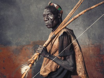 A Hadza elder wears a roughly tanned wild-animal skin over a T-shirt. The skin strips on his bow reinforce his weapon while the furs attest to his recent kills. His headband is not traditionally Hadza; members of the tribe have begun to adopt styles from neighboring groups.
