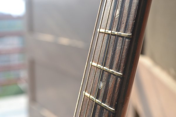 Strings of a guitar lying in room. thumbnail