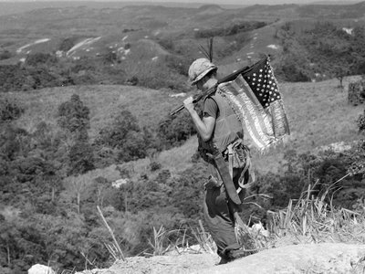 A U.S. Marine carries an American flag on his rifle during a recovery operation in summer 1968