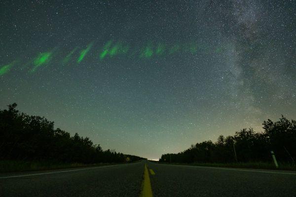A crossroads between road, aurora borealis and the Milky Way. thumbnail