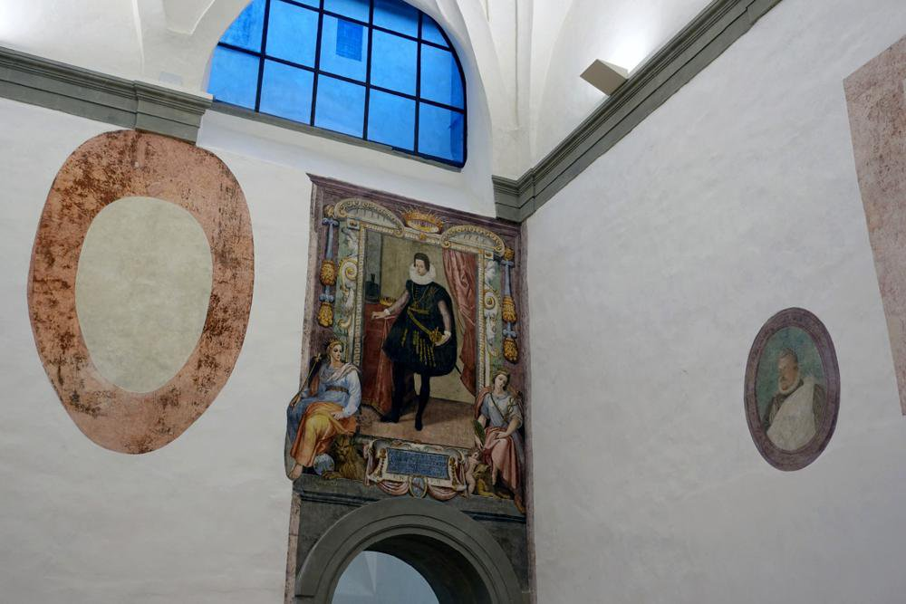 A white plaster-walled room with one archway, over which a large square fresco hangs, depicting a man in black garb standing in front of a luxurious background