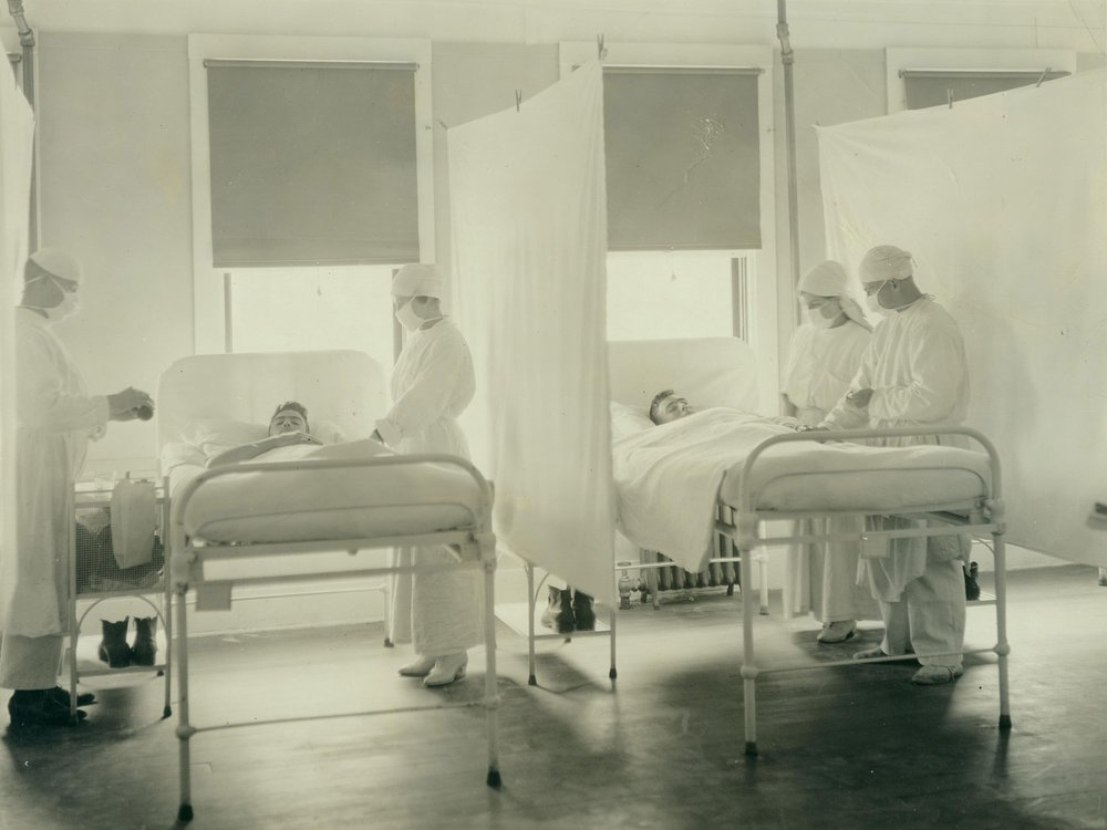 A black and white photograph of patients being treated by nurses during the 1918 influenza pandemic in a ward