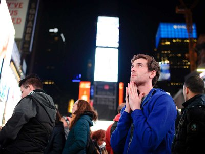 A young man watches incoming presidential election results in 2016 on the giant screens of Times Square.