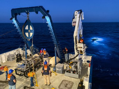 The Nautilus, a research vessel operated by the Ocean Exploration Trust, and the ROV Hercules (in the water) on the hunt for a cancer-busting marine bacteria.