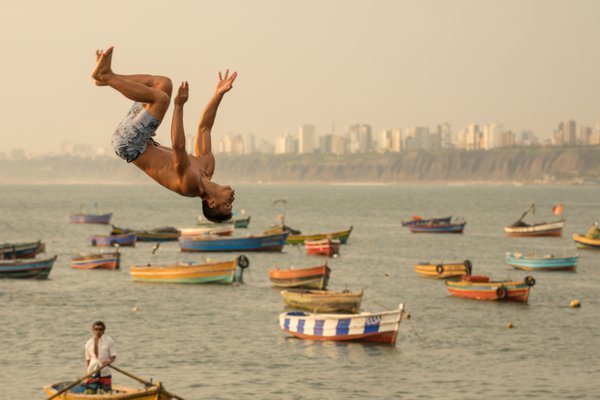 A young man back flips from a pier in the fishing village of Chorillos in Lima, Peru.