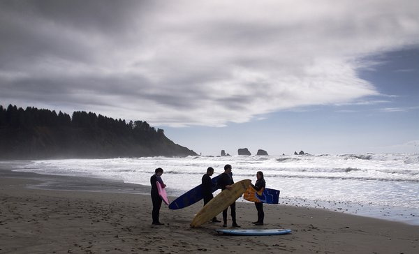 A group of surf riders prepare to enter the water on a beach near the remote tribal village of La Push, WA. thumbnail