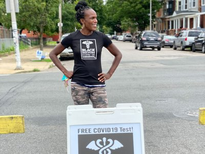 Surgeon Ala Stanford takes a pause from testing while standing near one of her group's signs in North Philadelphia.
