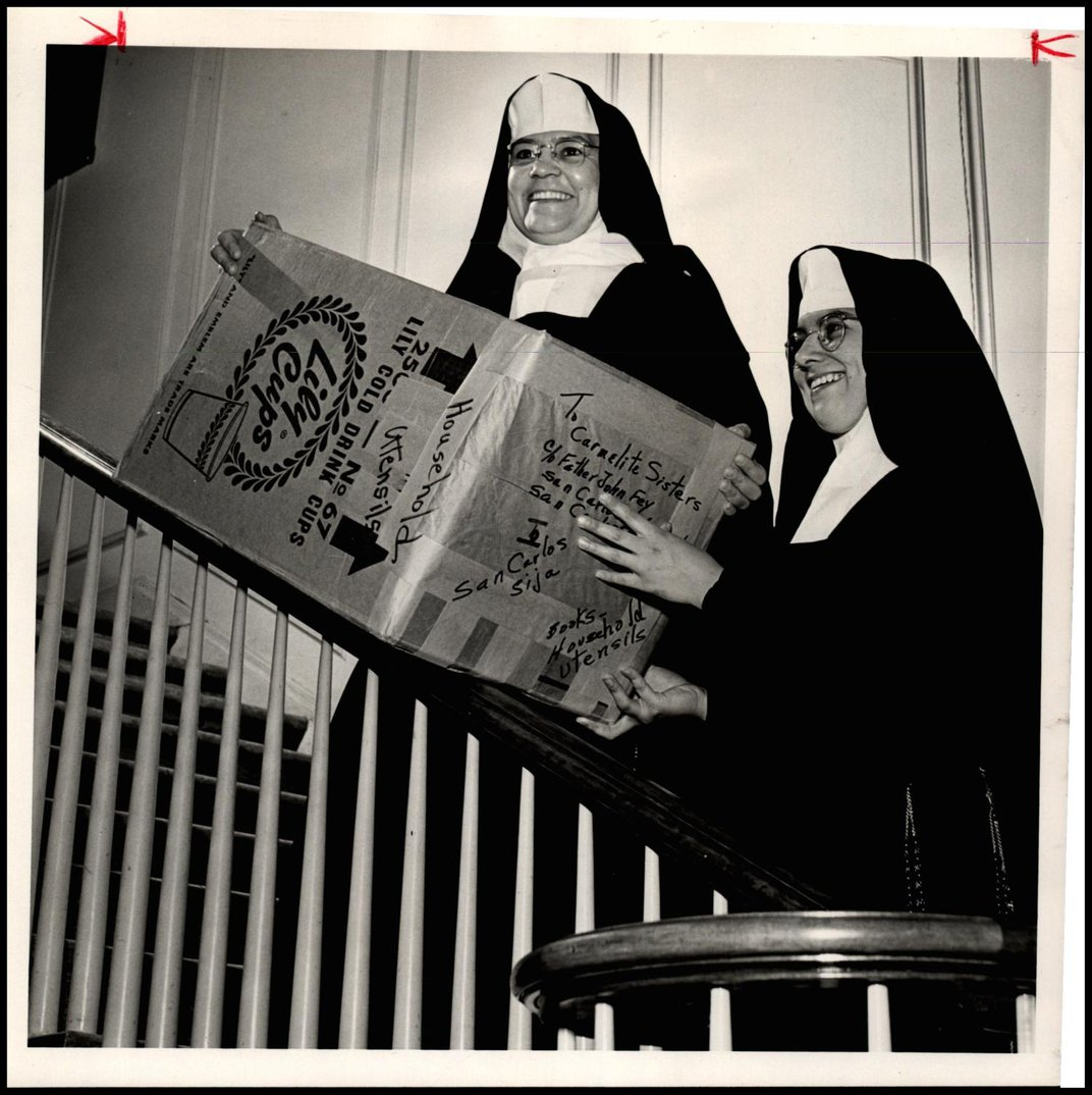 Two nuns on a staircase hold a box.