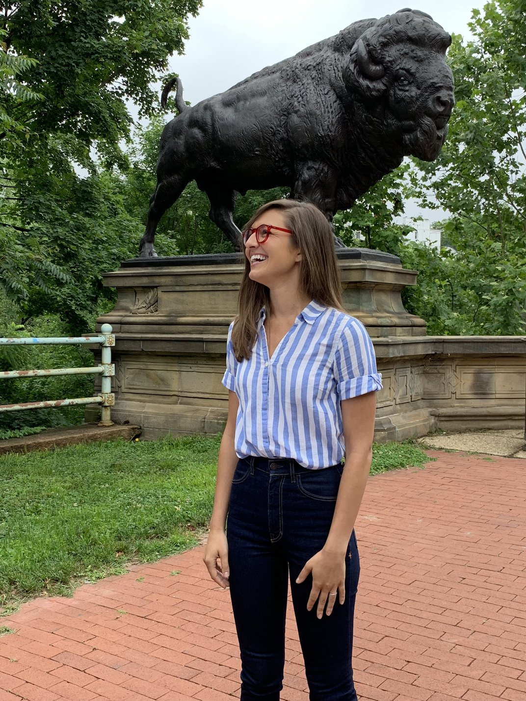 A photograph of a woman standing in front of a sculpture of a buffalo.