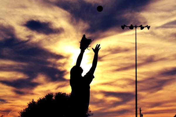 Softball player catching the ball at sunset. thumbnail