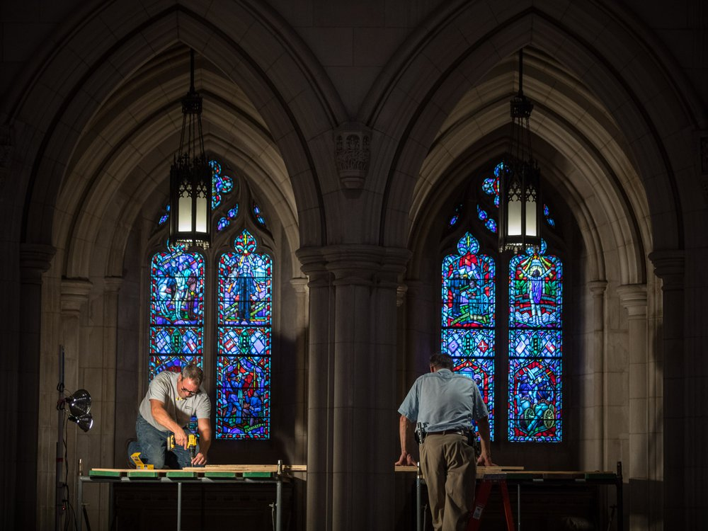 Workers erect scaffolding near two tall stained glass windows, which shine with blue light