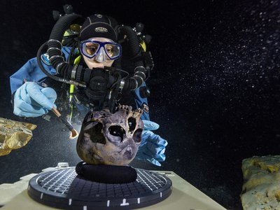 Diver Susan Bird works at the bottom of Hoyo Negro, a large dome-shaped underwater cave on Mexico's Yucatán Peninsula. She carefully brushes the human skull found at the site while her team members take detailed photographs.