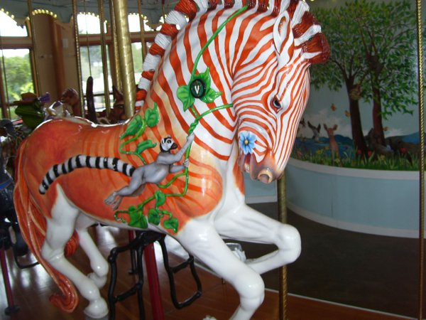 An orange-striped horse rearing  up wildly while still attached to a pole on a carousel in Albany, Oregon thumbnail