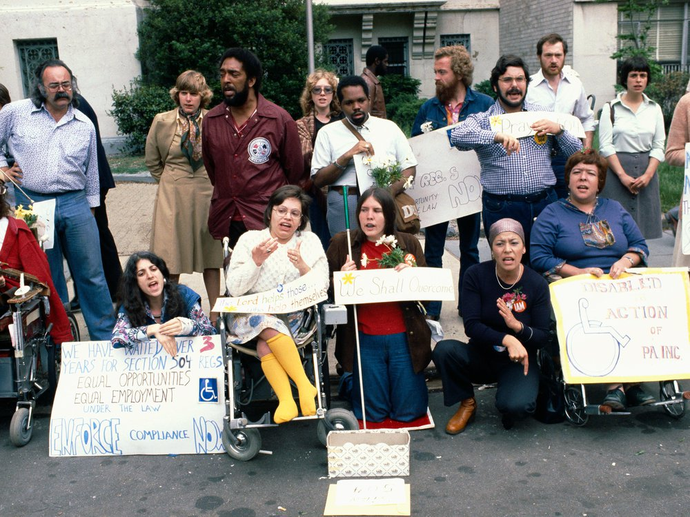 """A color photograph of a group of protesters, including Judy Heumann, who is wearing bright yellow stockings. One sign reads: """"We have waited over 3 years for Section 504 Regs...ENFORCE compliance NOW"""""""