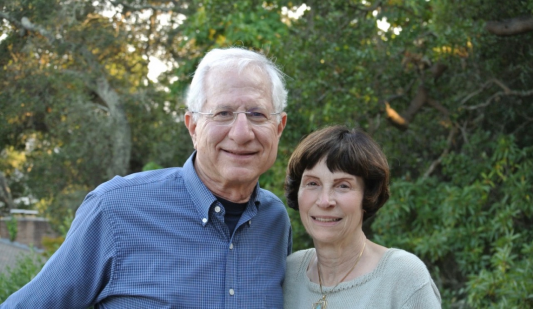 Portrait of a man and woman standing outside in front of green trees.