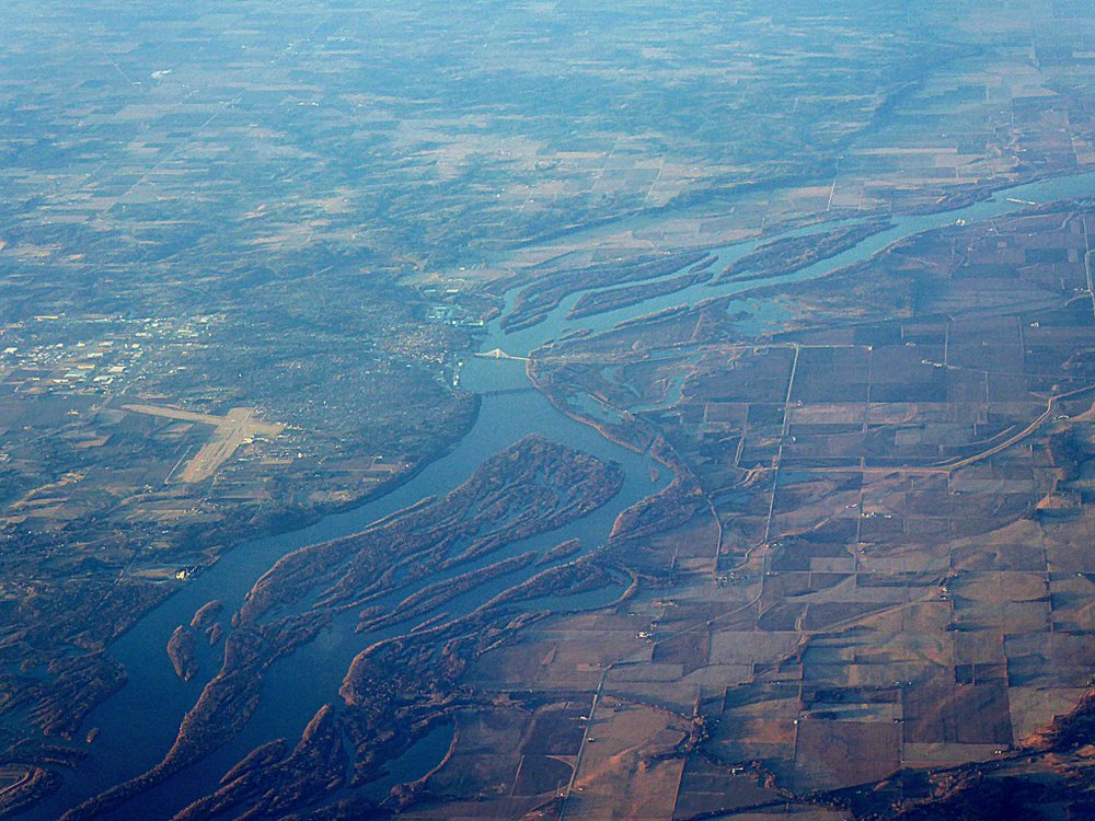 An aerial photo of the Mississippi River flowing through Iowa. The river runs through the middle of the photo, separating patches of fields on the right and more urban and suburban areas on the left.