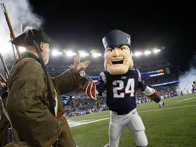 New England Patriots mascot Pat Patriot high-fives a minuteman after an NFL football game against the New York Jets, Oct. 16, 2014.