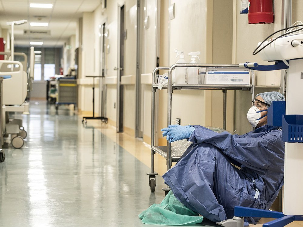 A female doctor wearing protective equipment sitting on the floor of a hospital hallway in Italy