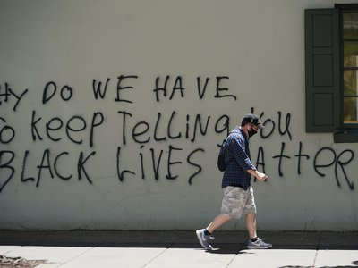 A man passes by graffiti on the side of the slave quarters of Decatur House in Washington, D.C.