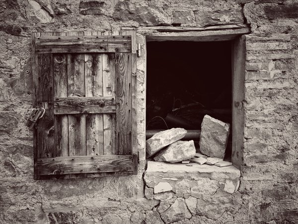 A window in an ancient stone wall in Italy thumbnail