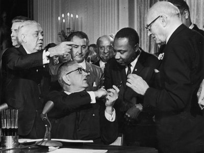 President Lyndon B. Johnson shakes hands with Martin Luther King Jr. at the signing of the Civil Rights Act.