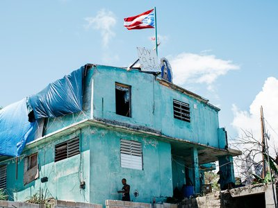 """A home on the storm-battered southeastern coast. The words on the sign, """"Yo voy a ti PR,"""" translate roughly to """"I'm rooting for you, Puerto Rico!"""""""