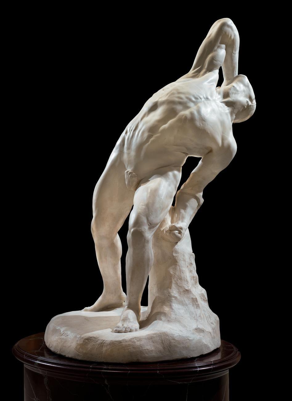 Statue of man leaning back over backward over a bolder