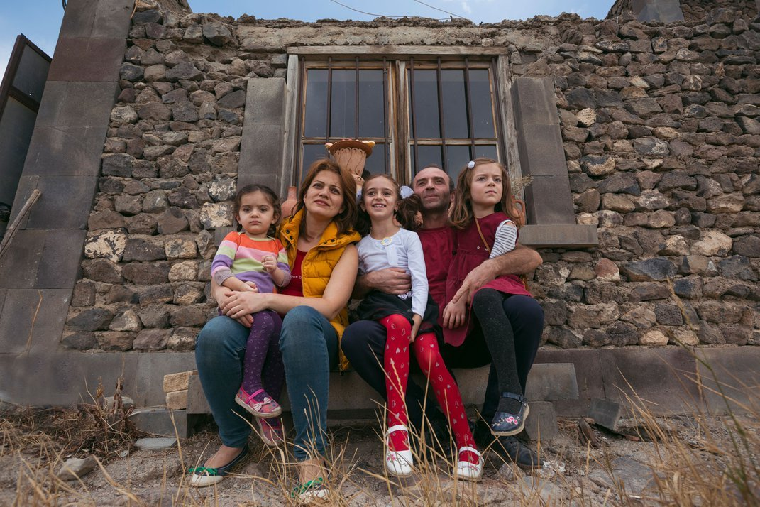 A man and his wife sit in front of a stone wall, their three young daughters sitting in their laps.