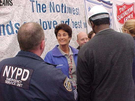 Woman with short brown hair smiles in a crowd of uniformed police offices