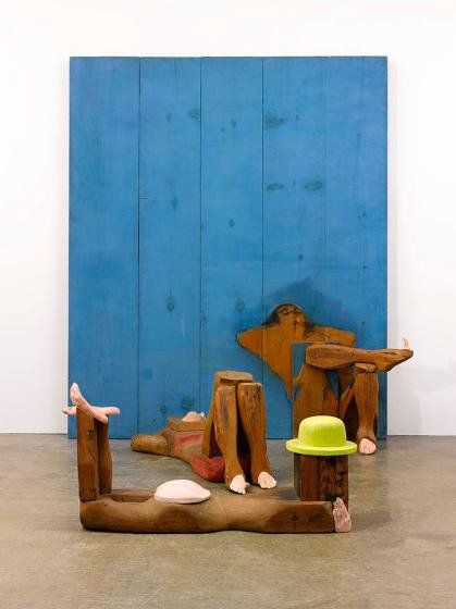 Wooden sculpture of three figures at the beach in various reclining positions. One figure wears a yellow hat and nothing else, one a red bikni, the other reads a book. Two  rest against a wooden panel painted blue.