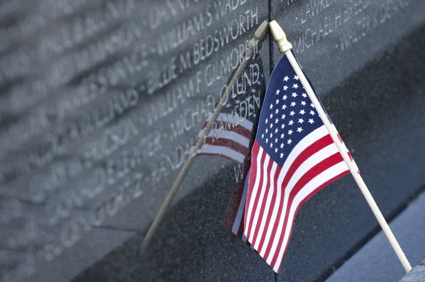 Flag left at VietNam Memorial to honor the fallen. thumbnail