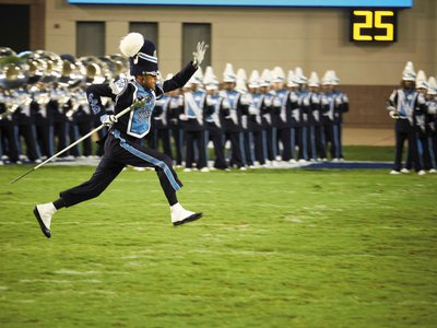 A Sonic Boom drum major dashes across the field.