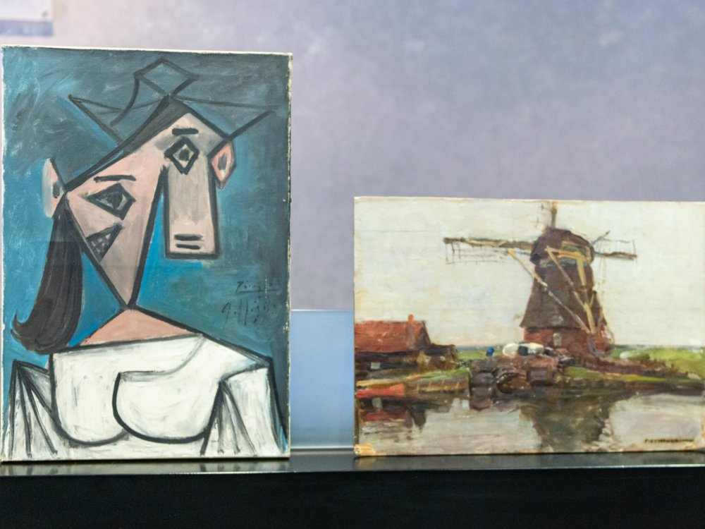 The Cubist bust portrait sits vertically next to the short horizontal Mondrian canvas, a gray- and green-toned depiction of a windmill over a body of water
