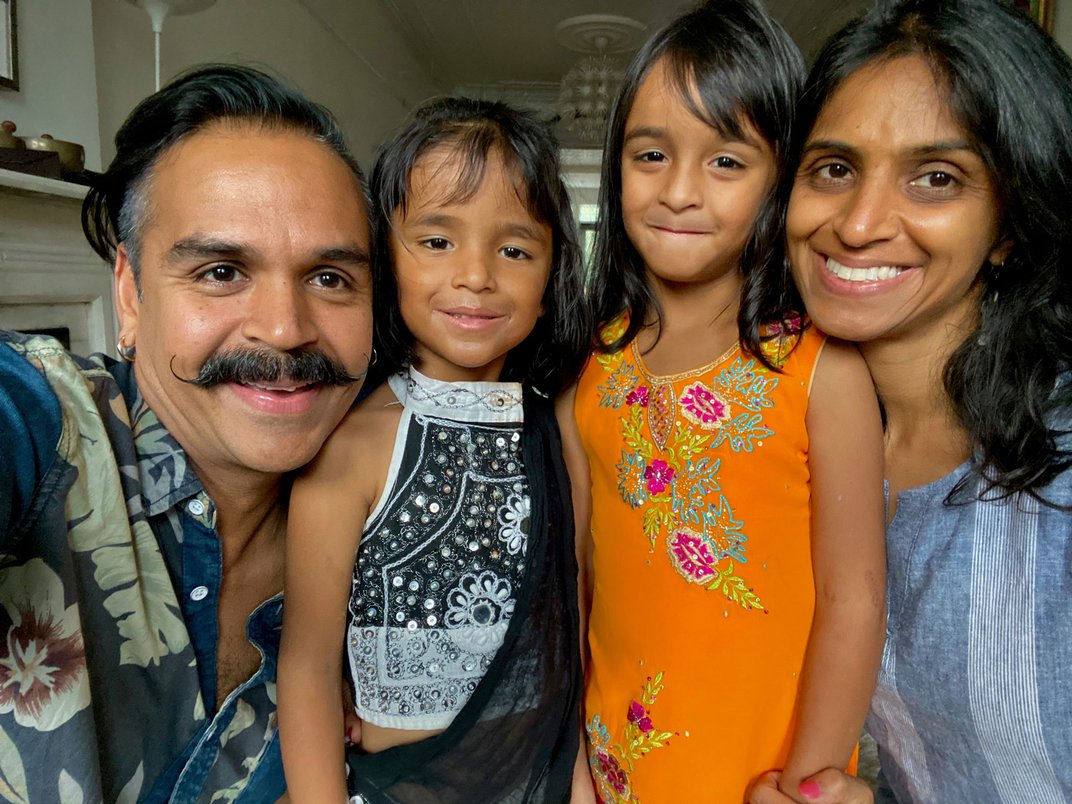 Family selfie, with Sunny Jain (author) on the left with handlebar mustache, gold earring, and blue Hawaiian print shirt. His wife is on the right, with long dark hair and a blue blouse. Their two young daughters are in between, all smiling.