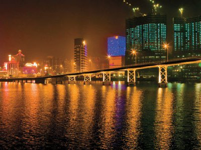 A view of Macau at night and the tail of the Dragon's bridge show a skyline full of potential and color as buildings continue to arise on reclaimed land