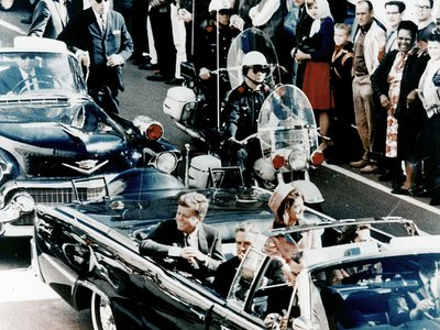 President John F. Kennedy in the presidential limousine before his assassination, on November 22, 1963, with his wife Jacqueline next to him.