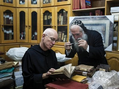 At the library of St. Mark's Syrian Orthodox Monastery in Jerusalem, Stewart and Abouna Shimon Can, a monk, view centuries-old Syriac manuscripts.