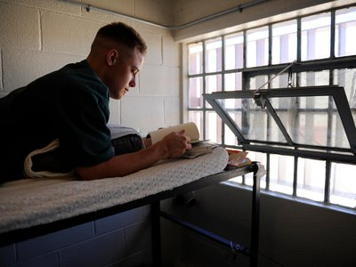 A Fremont Correctional Facility inmate reading a book on the top bunk of his cell.